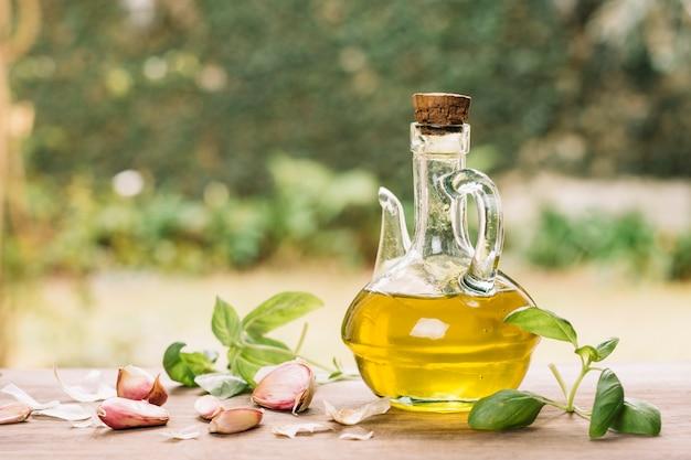 Блестящая бутылка оливкового масла с грацилом на открытом воздухе