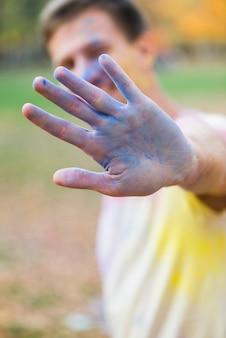 ホーリーで青い手を示す男