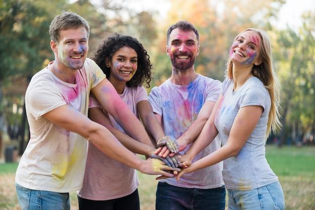 Средний снимок людей, соединяющих руки