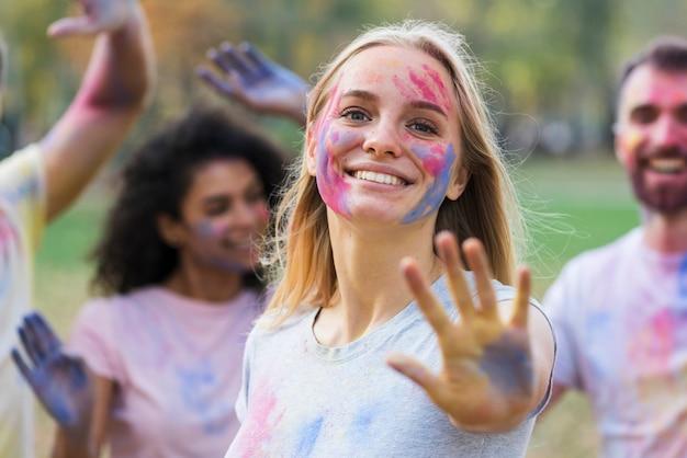 Улыбается женщина, показывая руку на холи с друзьями