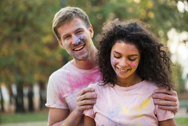 Пара окрашена в цвет, позируя в холи