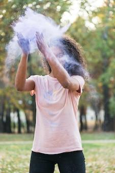 Средний снимок женщины, создающей голубую пыль