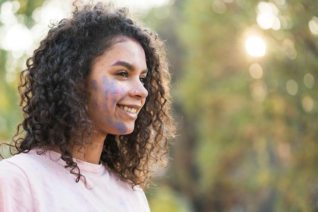 彼女の顔に青い絵の具を持つ女性の側面図