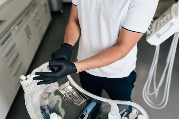 Крупный план стоматолога, надевая хирургические перчатки