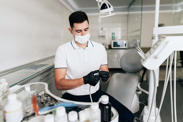 Средний снимок стоматолога, проверяющего хирургическое оборудование