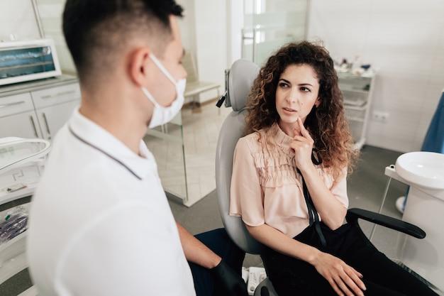 Женщина указывая на зуб в офисе дантиста