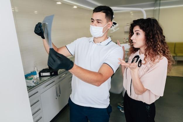 Пациент в офисе стоматолога, глядя на рентгенографии