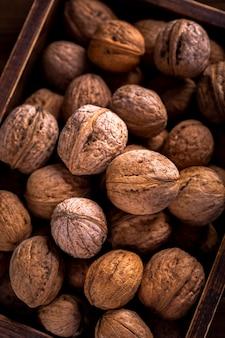 Закройте вверх по грецким орехам в деревянной коробке