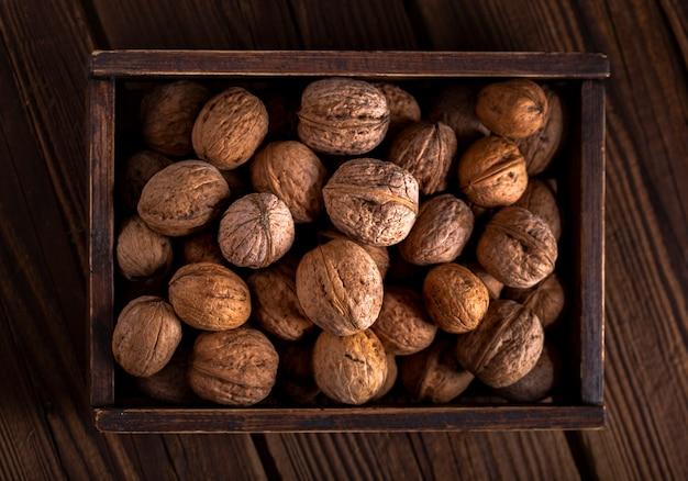Плоские лежал грецкие орехи в деревянной коробке
