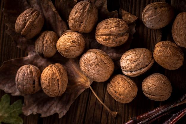 Закройте вверх по грецким орехам на деревянном столе с листьями