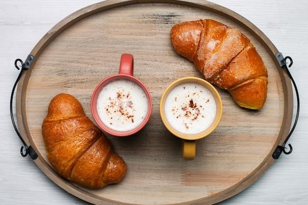 Плоские кофейные чашки с круассанами