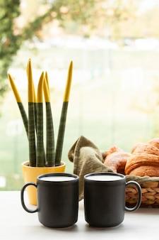 Вид спереди кофейные чашки с круассанами