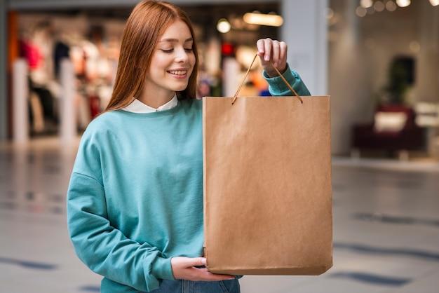 紙袋を示す赤毛の女性
