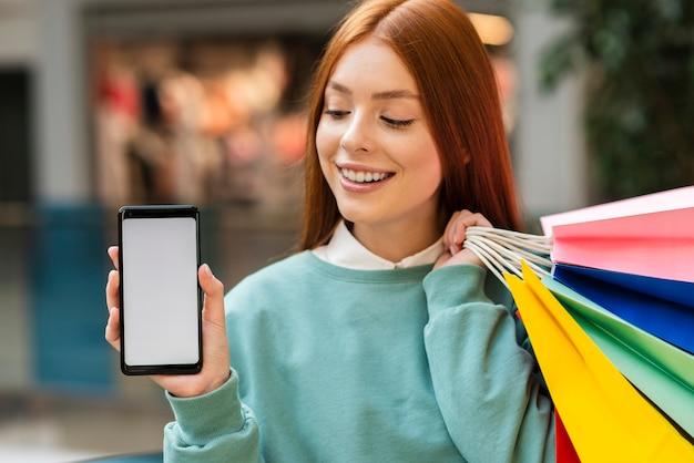 Рыжая женщина держит телефон макет