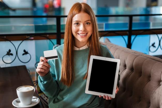 クレジットカードと写真のモックアップを保持している女性の笑みを浮かべてください。
