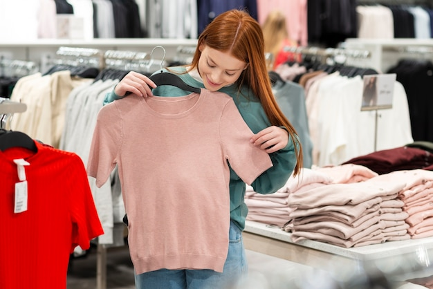 Рыжая женщина примеряет одежду
