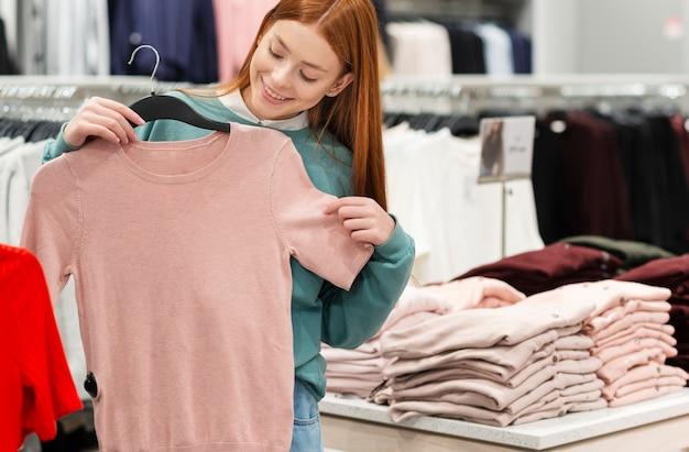 Красивая женщина пробует одежду