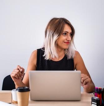 Женщина вид спереди на работе с помощью ноутбука