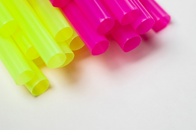 Вид сверху желтые и фиолетовые соломинки на столе