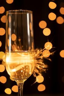 Боковой вид фейерверков и бокал с шампанским