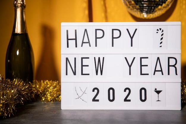 シャンパンボトルの横にある幸せな新年サイン