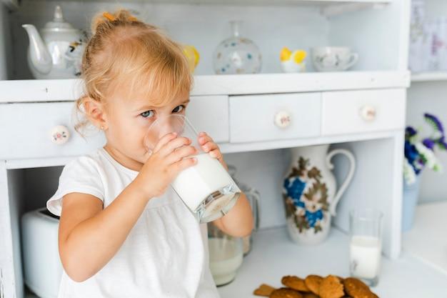 Очаровательная маленькая девочка пьет молоко