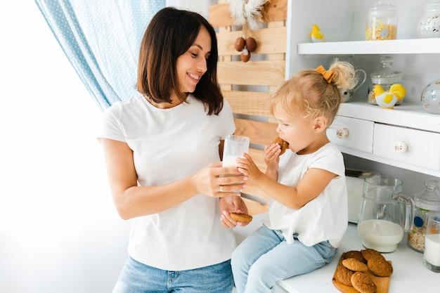 Очаровательная маленькая девочка ест печенье