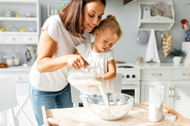 母と娘のボウルに牛乳を注ぐ