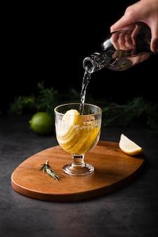 Рука наливает шампанское с ломтиком лимона