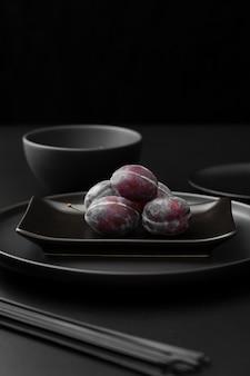 Темные тарелки со сливами на темном столе