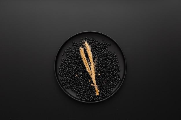 暗い背景に豆と暗いプレート