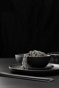暗い皿の上のパスタと黒のボウル