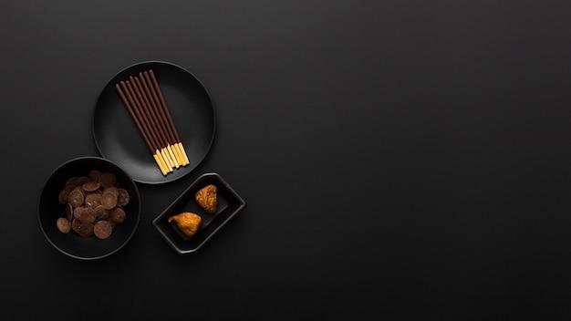 Тарелки с шоколадными палочками на темном фоне