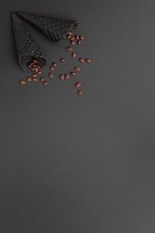 コーヒー豆とコピースペースを持つブラックアイスクリームコーン