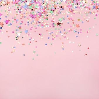 コピースペースとピンクの背景にカラフルな星紙吹雪