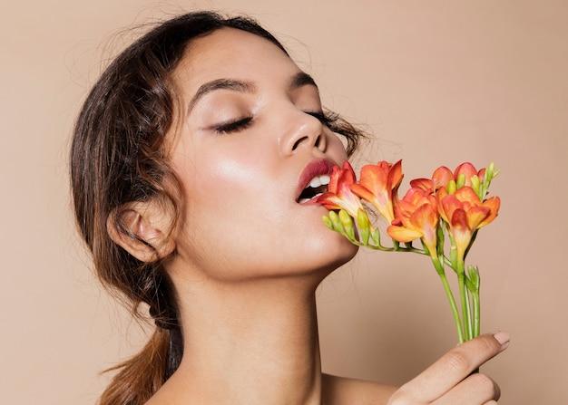 活気のある花を持つかなり若い女性