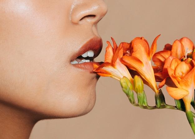 鮮やかな花を持つ若い女性の唇
