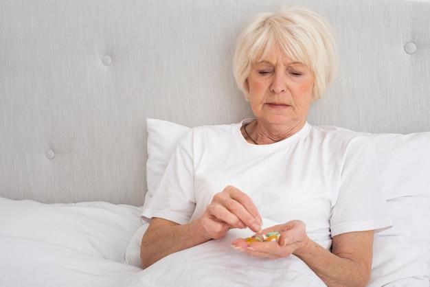 Пожилая женщина держит таблетки