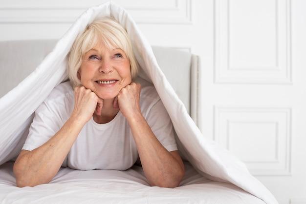 毛布の下に座っている年配の女性