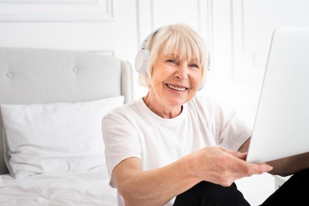 Счастливая старшая женщина держит ноутбук