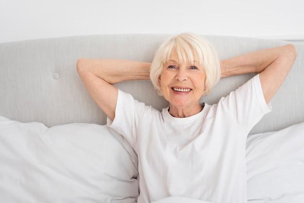 Улыбающаяся пожилая женщина сидит в спальне