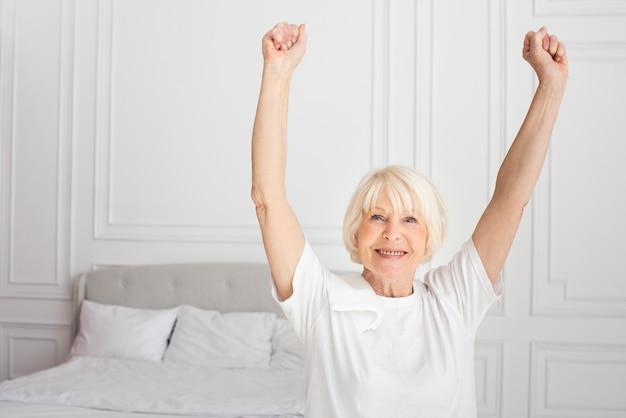 Улыбающаяся старшая женщина сидит в спальне
