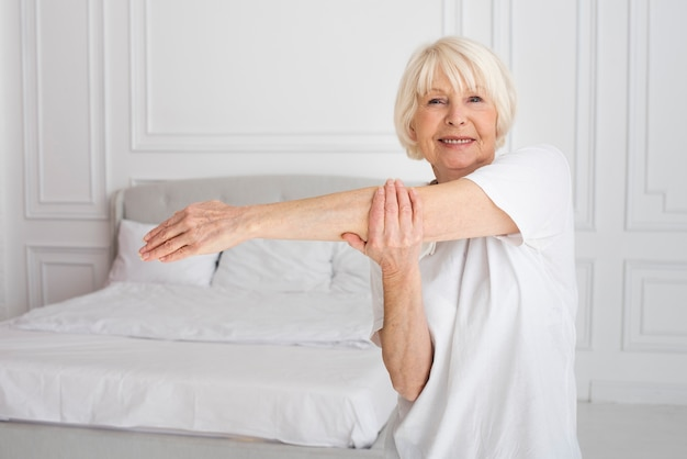 Пожилая женщина занимается спортом в спальне