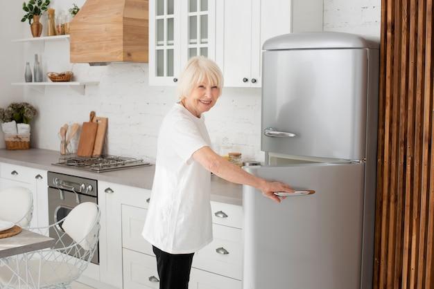 Пожилая женщина открывает дверь холодильника