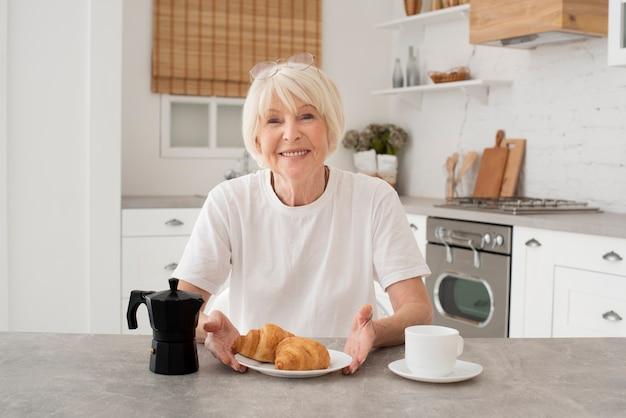 Счастливая пожилая женщина сидит на кухне
