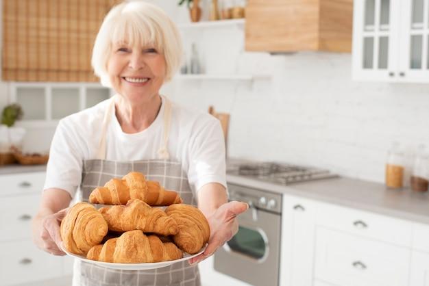 Улыбающаяся пожилая женщина держит тарелку с круассанами