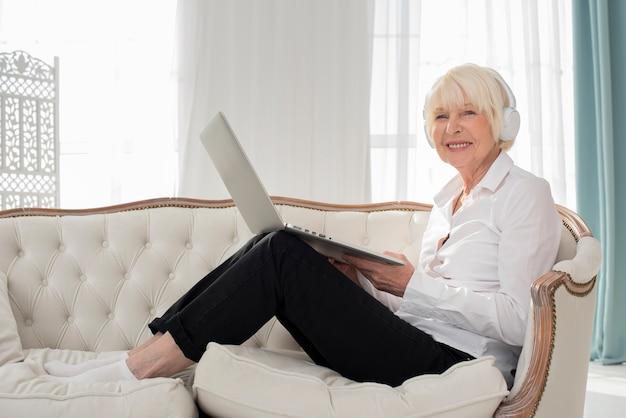 Пожилая женщина сидит на диване с наушниками и ноутбуком