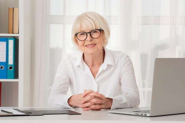 Улыбающаяся пожилая женщина в очках сидит в своем кабинете