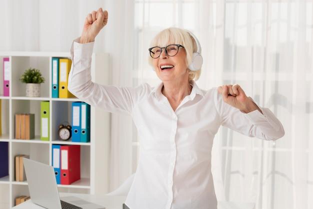 年配の女性が彼女のオフィスで音楽を聴く