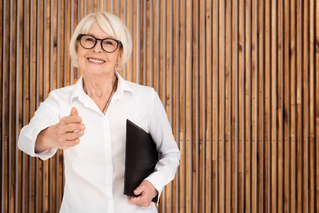 木製の背景にクリップボードを持つ高齢者の女性